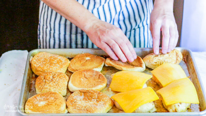 Placing cheese on chicken and buns on the sheet tray.