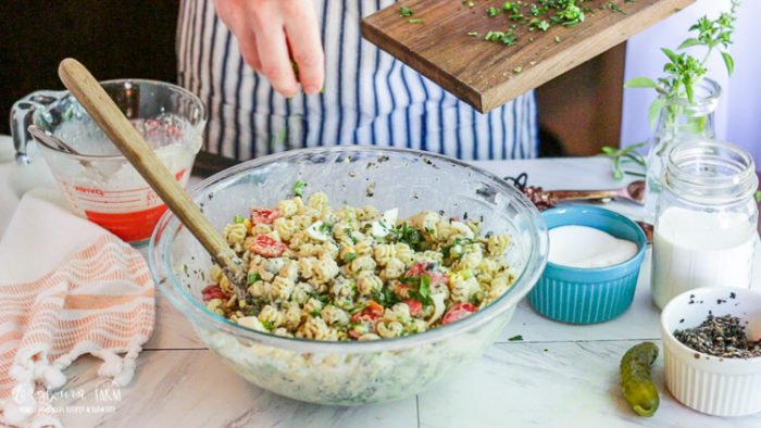 Garnishing the easy macaroni salad with herbs.