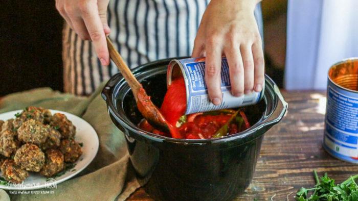 Adding tomato sauce to meatball sandwiches.