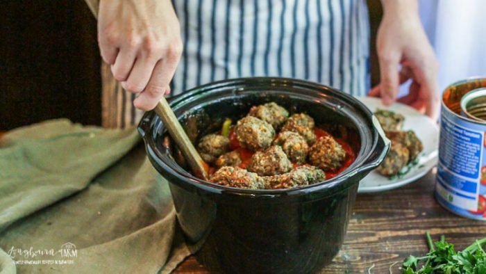 Adding meatballs to the sauce for meatball sandwiches.