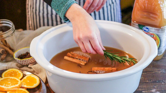 Adding rosemary to mulled cider.