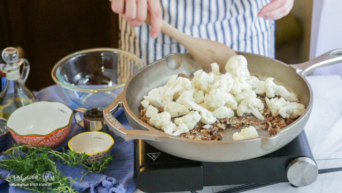 Mixing cauliflower and pecans in a GRIZZLY cast iron pan.