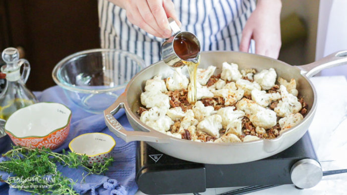 Pouring honey into the pan roasted cauliflower.