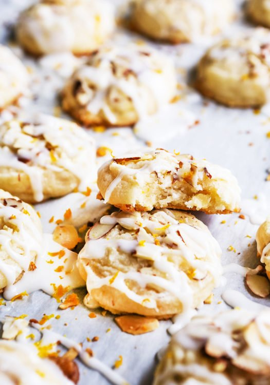 These Almond Cookies are melt-in-your-mouth delicious and super easy to make! The cookies have a chewy texture with crunchy bits of almond. They are topped with an almond glaze and a touch of orange zest that will leave you wanting more (and more and more)! #almondcookies #almondcookiesrecipe #almondcookierecipe #almondcookiesrecipeeasy #chocolatealmondcookies #christmascookies