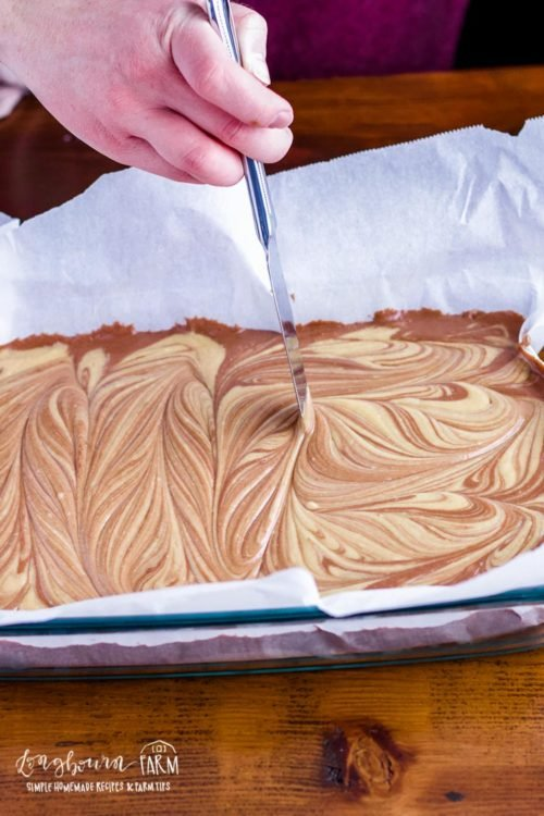 Swirling peanut butter chocolate fudge into the pan.