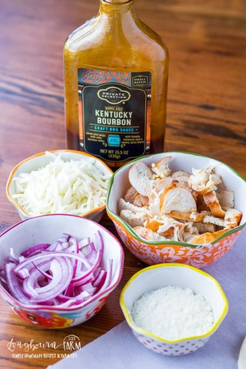 Ingredients for BBQ chicken pizza recipe on a wood table.