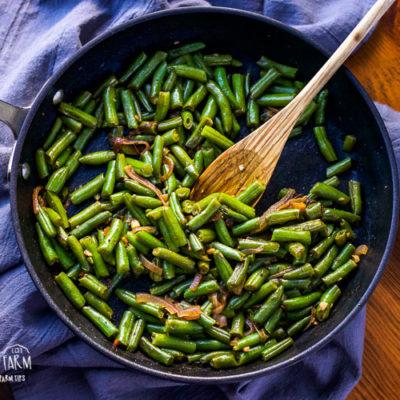 Frozen green beans in a saute pan.