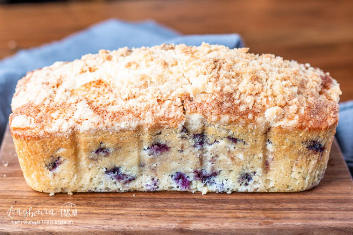 Blueberry quick bread with a crumb topping on a board.