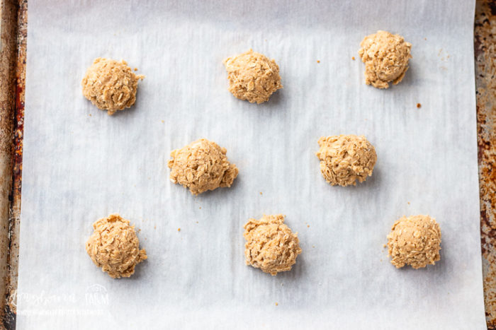 Oatmeal cookie dough on a baking sheet ready to bake.