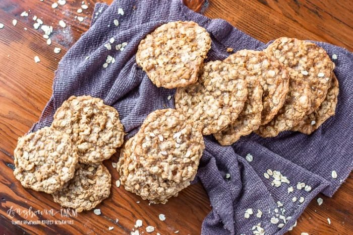 Chewy homemade oatmeal cookies in a pile on a table with a towel.