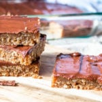 Chocolate peanut butter cookie bars stacked on a cutting board.