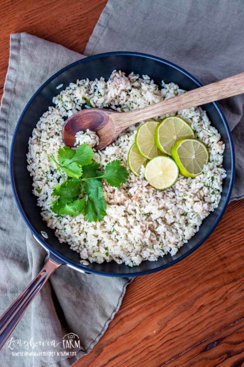 Cilantro lime rice recipe in a black pan with a wooden spoon.