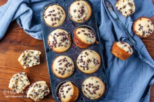 Homemade chocolate chip muffins in a muffin tin with a grey linen behind them.