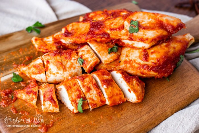 Oven baked bbq chicken on a cutting board.