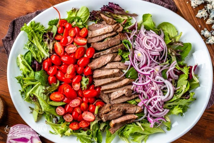 Steak salad layered on a white platter.