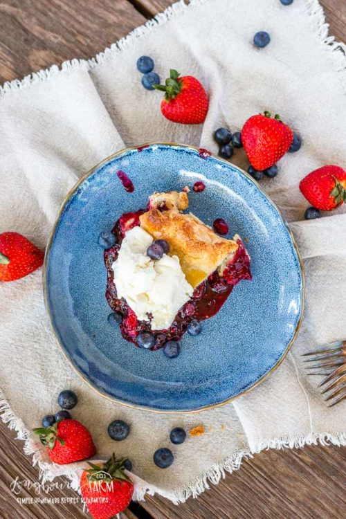 Slice of mixed berry pie on a blue plate.