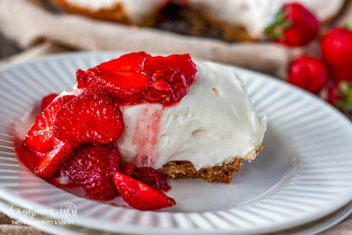 Slice of easy no bake cheesecake on a plate topped with strawberries.