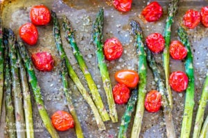 Oven roasted asparagus and tomatoes on a sheet pan sprinkled with parmesan cheese.