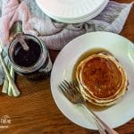 Butter maple syrup over pancakes sitting next to the plate in a jar.