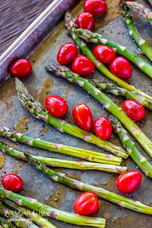 Asparagus and cherry tomatoes on a sheet tray drizzled with olive oil.