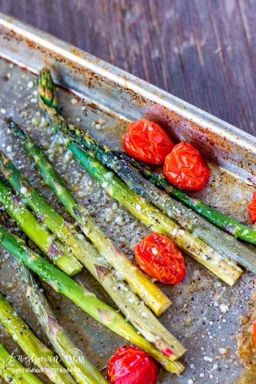 Close-up of roasted asparagus and tomatoes on a sheet tray.