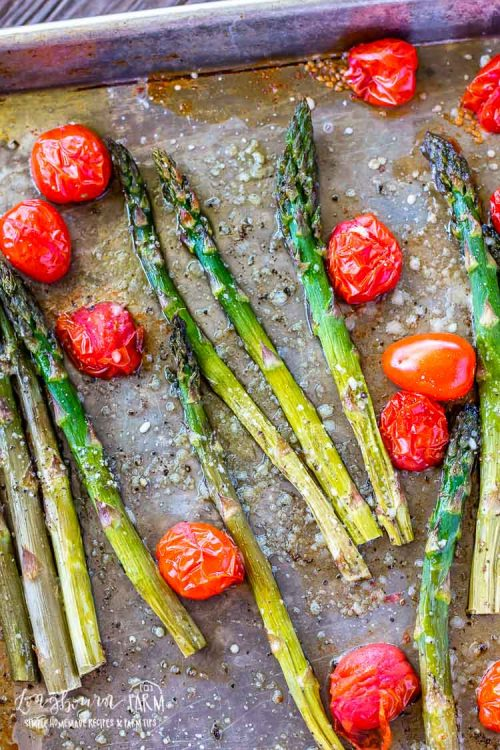 Asparagus and tomatoes on a sheet tray after being roasted and sprinkled with parmesan cheese.