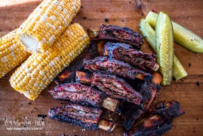 Smoked beef ribs paired with corn on a cutting board.