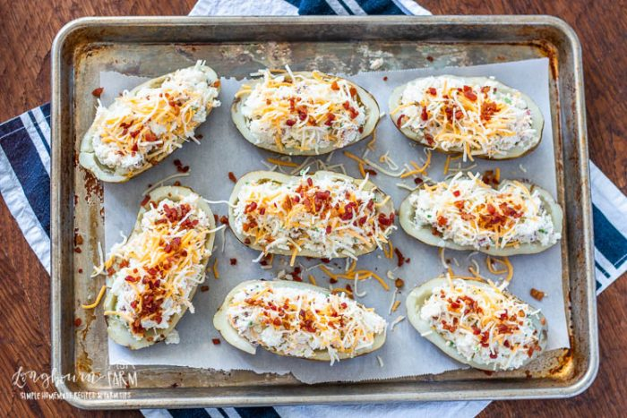 Prepared twice baked potatoes on a sheet pan.