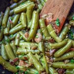 Canned green beans with bacon and onions in a pan with a wooden spoon.