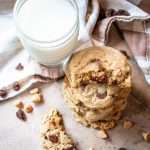 Easy chocolate chip peanut butter cookies staked next to a glass of milk, top view.