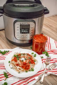 Instant pot marinara in front of an instant pot in a jar.