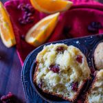 Close-up of a broken orange cranberry muffin.