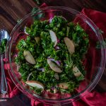 Kale apple salad in a bowl sitting on a red towel.