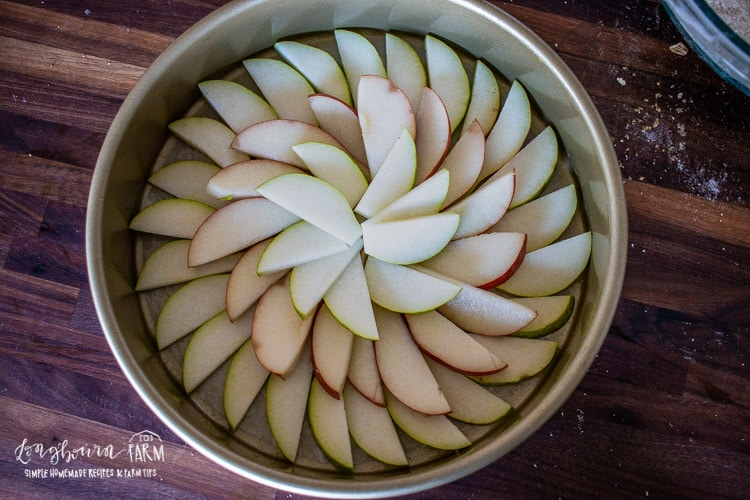Sliced pears lined up in a cake pan.