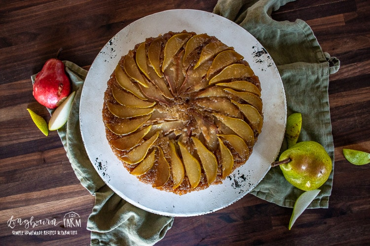 Upside down pear cake turned upside down on a cake tray.