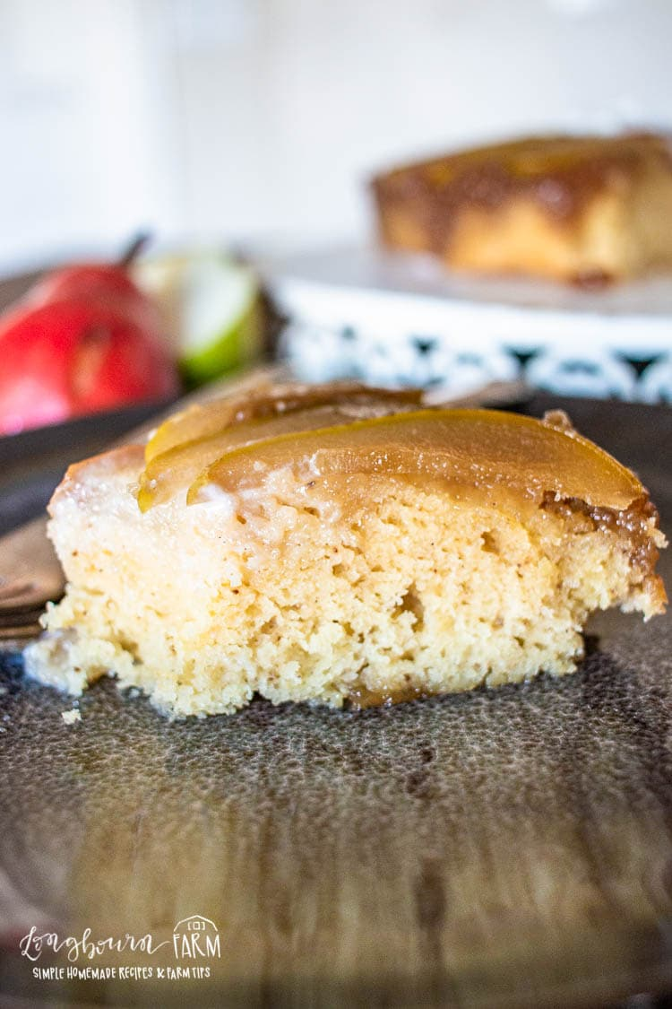 Slice of upside down pear cake on a plate.