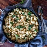 White bean and kale pasta in a frying pan on a grey towel, vertical.