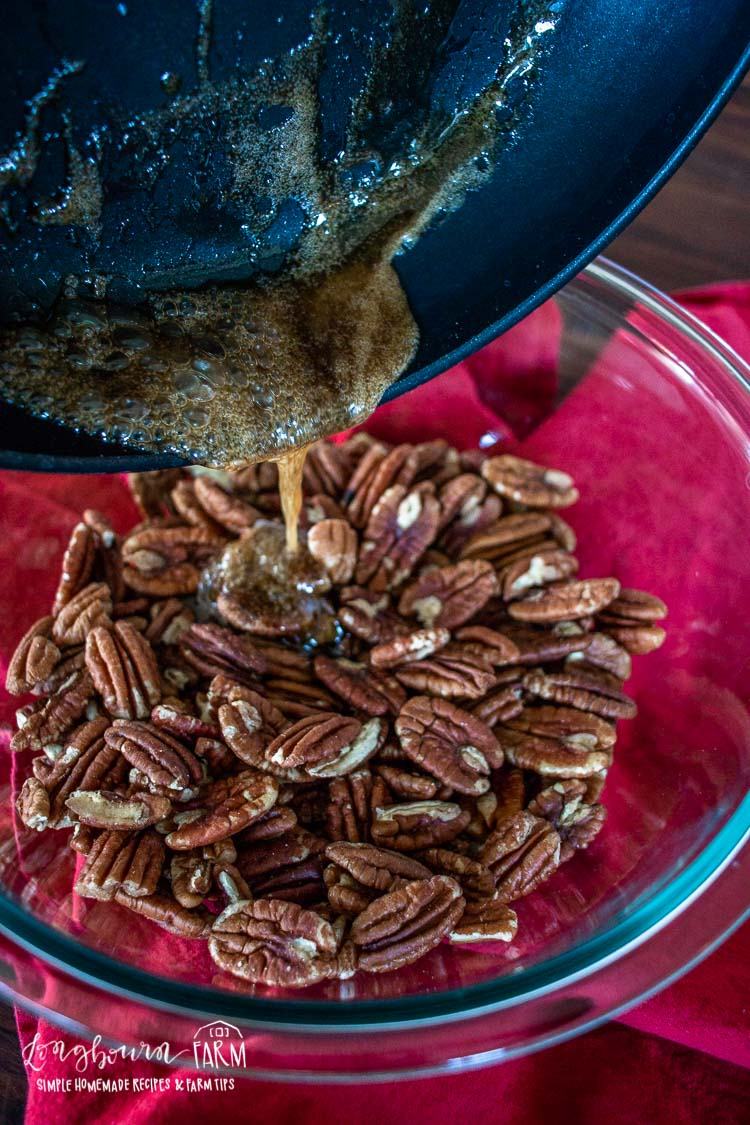 Pouring rum mixture over the toasted pecans.
