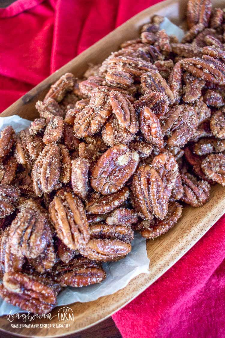 Rum spiced pecans in a wooden dish on a red towel, vertical.