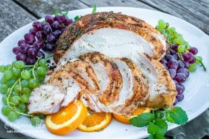 coin sliced smoked and seasoned turkey breast on a serving platter with grape bunches and sliced oranges