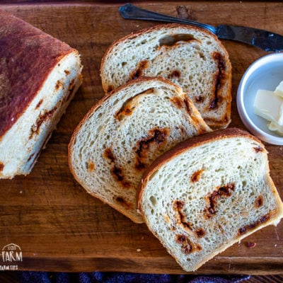 three slices of cinnamon bread on a cutting board with butter in a bowl and half a loaf of uncut bread