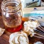 whipped honey butter on a whisk with a jar of honey and sticks of butter
