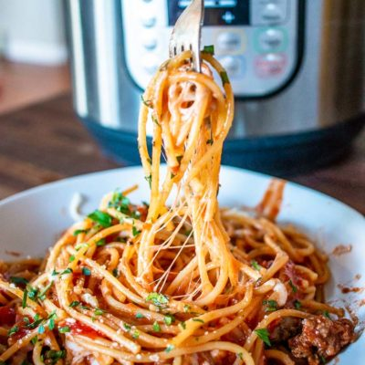 forkful of spaghetti over a bowl of spaghetti in front of the instant pot