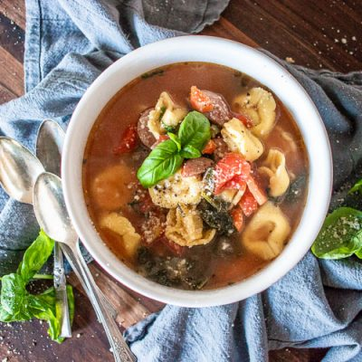 a bowl of tortellini soup with garnises, spoons and a tea towel underneath