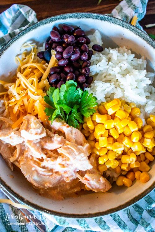 an upclose view of the mexican chicken in a bowl with cheese, corn, black beans, and white riceand garnish