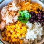 an upclose view of the mexican chicken in a bowl with cheese, corn, black beans, and white rice and garnish