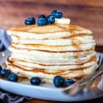 a upclose side view of a stack of pancakes on a plate with syrup, fresh blueberries, a slab of butter and two forks