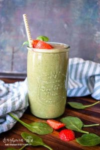 a delicious green smoothie with strawberry slices and spinach leaves scattered