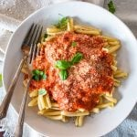 a plate full of pasta with marinara sauce cheese and garnishes and two forks