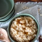 maple and brown sugar oatmeal in a serving bowl with a wooden spoon off to the side